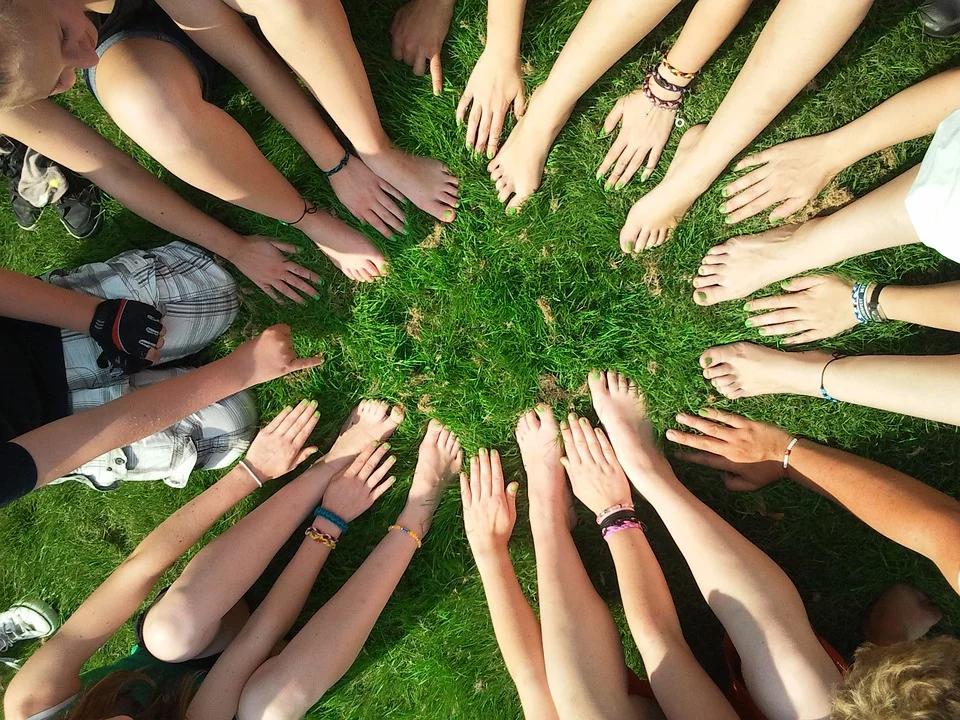 dłonie i stopy różnych ludzi ułożone w koło