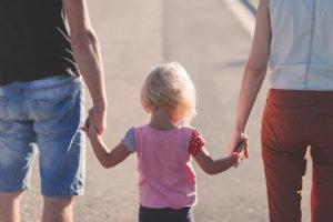 dziecko pośrodku trzymające za ręce mąmę i tatę